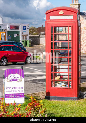 Old red telephone box converted to book lending library in conservation village, East Saltoun, East Lothian, Scotland, UK - Stock Photo