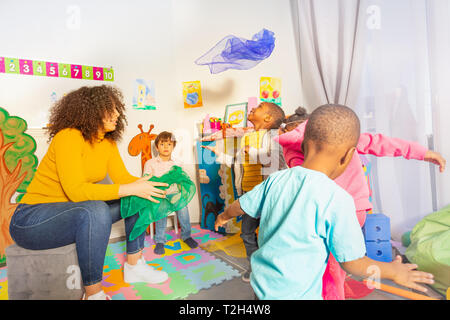 Fun active game with group little kids throwing fabric in the air in nursery school - Stock Photo