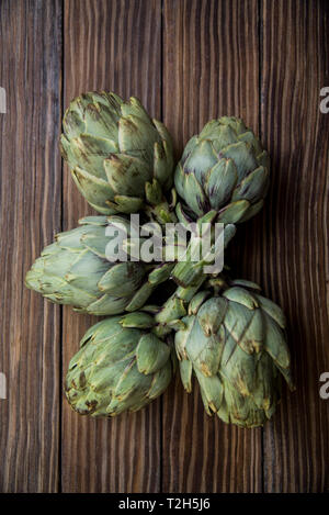 artichokes on old wooden table - Stock Photo