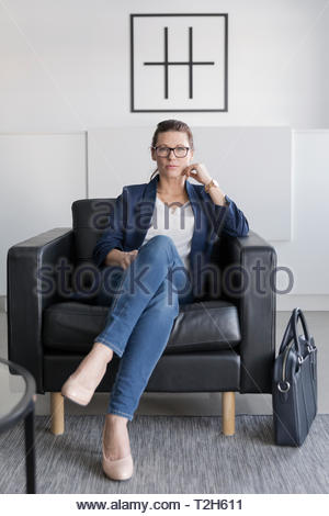 Portrait confident businesswoman sitting in leather armchair in office lobby - Stock Photo
