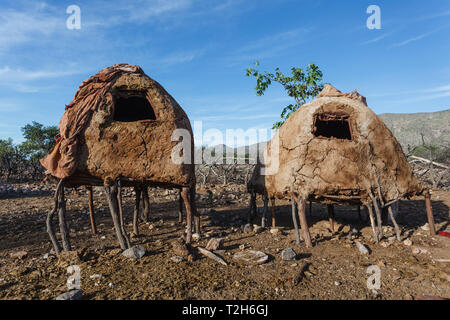 Closeup of two Himba tribe homes built of mud on stilts in Damaraland - Stock Photo