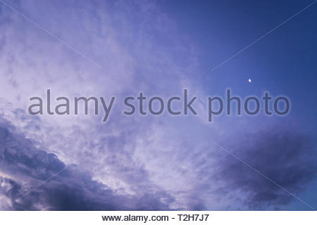 Blue and purple evening sky with different types of clouds like Cirrocumulus, Altocumulus and Cumulus. Small crescent moon behind. - Stock Photo
