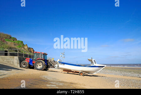 A fishing boat and tractor by the seawall on the North Norfolk beach at East Runton, Norfolk, England, United Kingdom, Europe. - Stock Photo