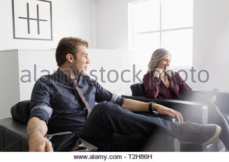 Business people waiting in office lobby - Stock Photo