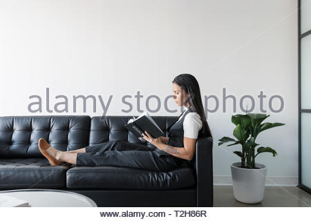 Businesswoman reading book on leather sofa - Stock Photo
