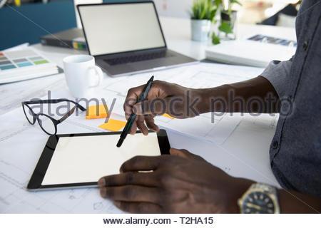 Close up architect using digital tablet - Stock Photo