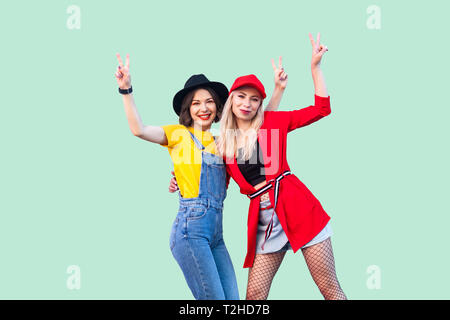 Best friends spending great time together. Portrait of two beautiful happy fashionable hipster girls standing and showing v sing, looking at camera. I - Stock Photo