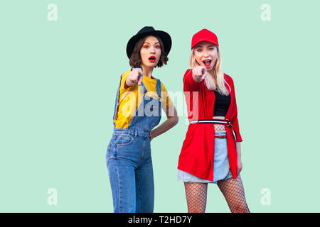 Best friends spending great time together. Two beautiful amazed fashionable hipster girls standing and pointing finger to you, looking at camera. Indo - Stock Photo