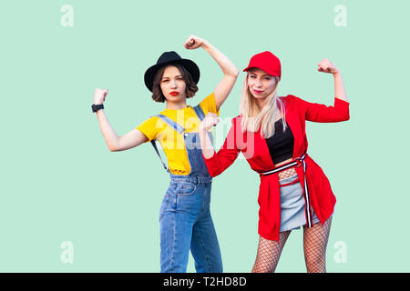 Best friends spending great time together. Portrait of two beautiful fashionable hipster girls standing and showing there power, looking at camera. In - Stock Photo