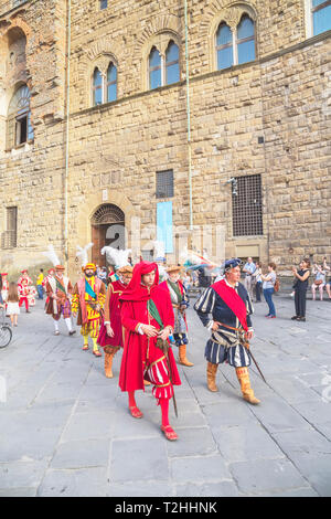 Men marching in costume during Calcio Storico Fiorentino festival at Piazza della Signoria in Florence, Tuscany, Italy, Europe - Stock Photo