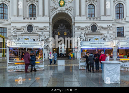 Shoppers at Christmas market stalls in Michaelerplatz, Vienna, Austria, Europe - Stock Photo