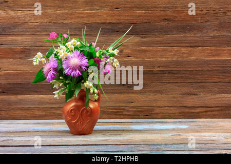bouquet of flowers of clover, cornflowers and Jasmine in a earthenware jug on a wooden table on a brown retro background with a copy space - Stock Photo