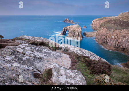 Dramatic cliffs, sea stacks and Enys Dodnan arch on the rugged north Atlantic coast, Lands End, Cornwall, UK - Stock Photo