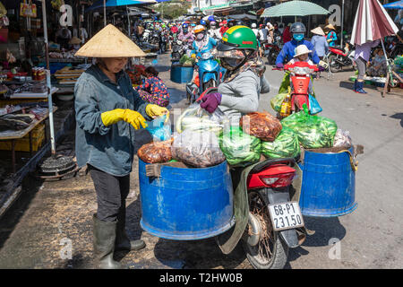 Vietnamese woman selling fresh fish from the panniers on a motorbike in Dinh Cau street market, Phu Quoc Island, Vietnam, Asia, - Stock Photo