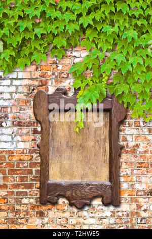 Wooden notice board against a brick wall covered in ivy - Stock Photo