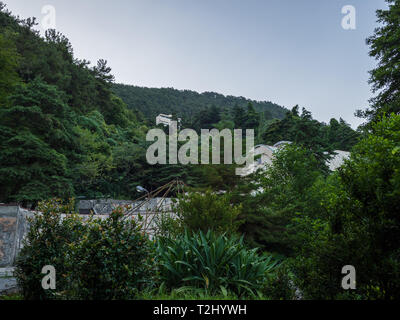 Old abandoned green park in front of the mountain. Blue sky in the evening. - Stock Photo