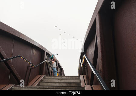 A man taking in the view from the Piety Street bridge, the pedestrian bridge to Cresent Park in the Byawater neighborhood of New Orleans, Louisiana. - Stock Photo