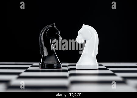 selective focus of chessboard with white and black knights isolated on black - Stock Photo