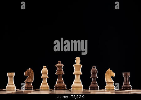 wooden chessboard with brown and beige chess pieces isolated on black