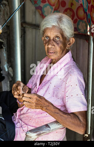 Galle, Sri Lanka - February 18th, 2019: Portrait of an senior woman threading a needle sitting outdoors of her workshop in Galle, Sri Lanka. - Stock Photo