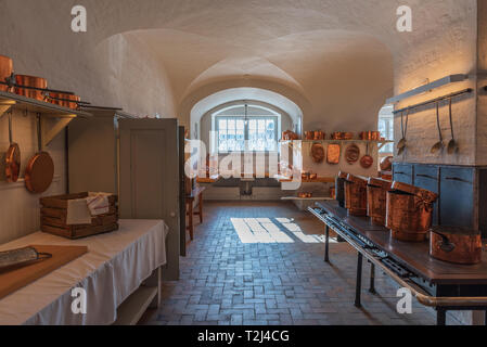Antique kitchen for professional use with numerous copper pots, horizontal image illuminated with lights in warm tones - Stock Photo