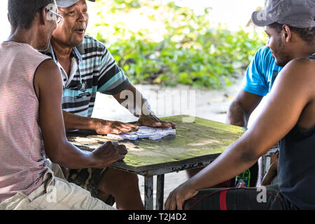 La Dique, Seychelles - February 4th, 2019: Four local men playinig domino outdoors in La Digue, Seychelles. - Stock Photo