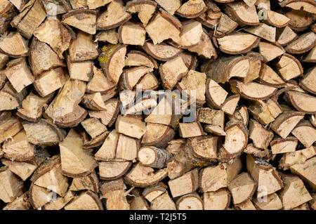dry chopped firewood logs in a pile, ready for winter - Stock Photo