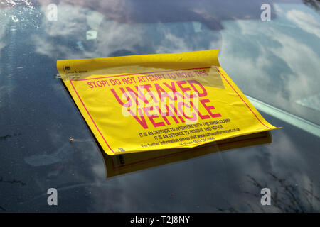 Untaxed vehicle sticker on the windscreen of a car immobilised at the roadside by a yellow DVLA clamp, for non-payment of road tax - Stock Photo
