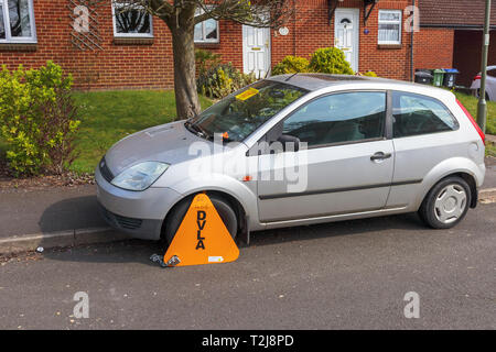 Untaxed car immobilised at the roadside by a yellow DVLA wheelclamp with sticker on the windscreen of non-payment of road tax - Stock Photo