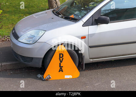 Untaxed vehicle immobilised at the roadside by a yellow DVLA clamp, for non-payment of road tax - Stock Photo