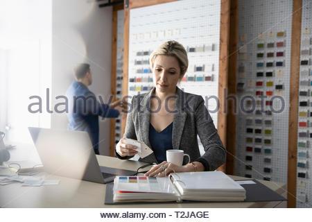 Female interior designer looking at paint swatches in design studio - Stock Photo