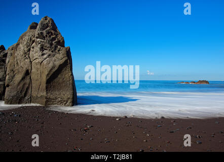Rock formation on Praia Formosa beach - famous public black sand beach on Portuguese island of Madeira - Stock Photo