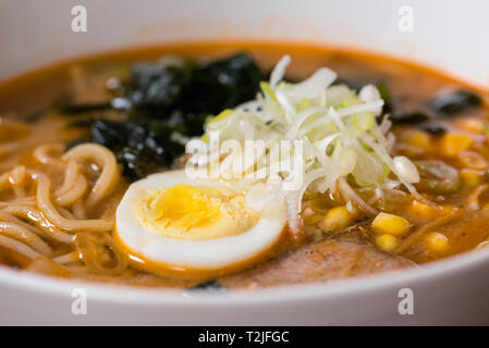Ramen miso of Meat with pork, soy milk, pork broth, black mushrooms, eggs, onions, corn, carrots and courgettes served in a bowl, close up details - Stock Photo