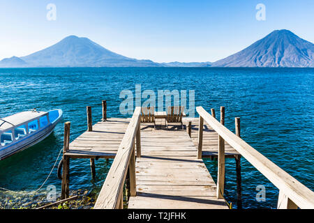 View from wooden jetty with seats across Lake Atitlan to Atitlan, Toliman & San Pedro volcanoes in Guatemalan highlands, Central America - Stock Photo