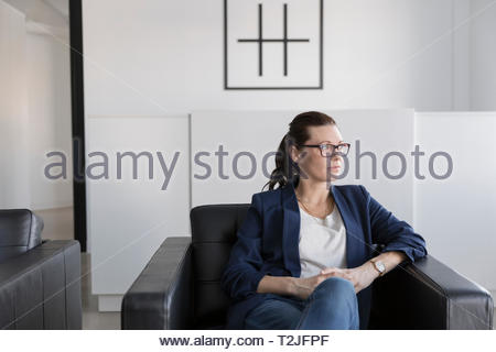 Thoughtful businesswoman sitting in leather armchair in office lobby - Stock Photo