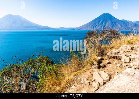 View from arid clifftop viewpoint across Lake Atitlan to Atitlan, Toliman & San Pedro volcanoes in Guatemalan highlands, Central America - Stock Photo