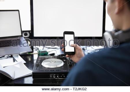 DJ using smart phone at digital mixing tables at desk - Stock Photo