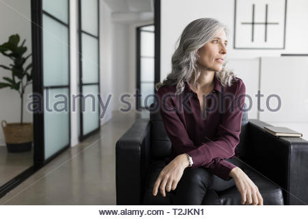 Thoughtful, forward looking businesswoman in office lobby - Stock Photo