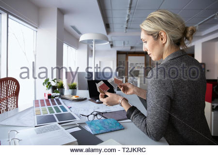 Female interior designer reviewing swatches in design studio - Stock Photo