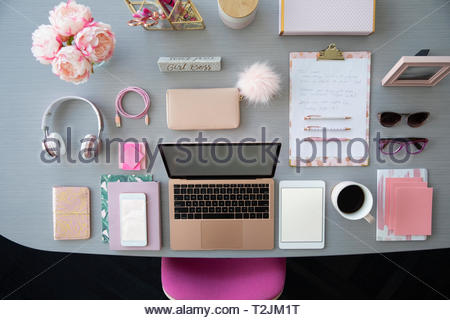 View from above pink laptop and office supplies on desk - Stock Photo