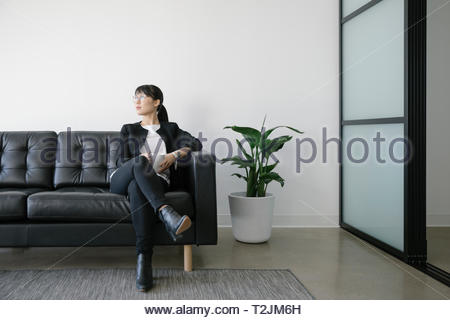 Thoughtful businesswoman with coffee on leather sofa - Stock Photo