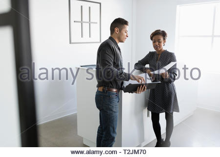 Business people discussing paperwork in office lobby - Stock Photo