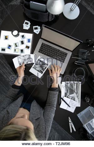 View from above female photographer working at laptop, reviewing photograph negatives - Stock Photo