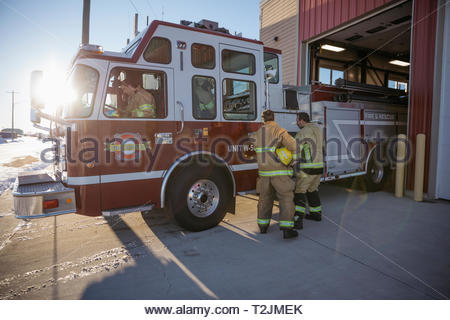 Firefighters at fire engine outside fire station - Stock Photo