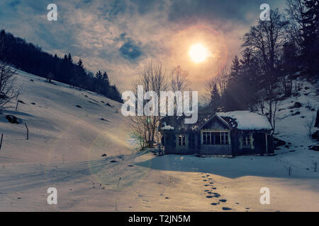 Small abandoned house found on the hills with footstepts in the snow guiding to the house shot in the mountains on a winter sunny day in Romania - Stock Photo