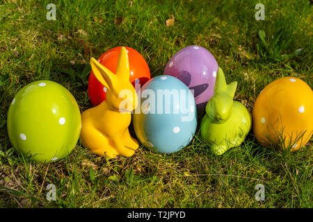 Colorful ceramic easter eggs and Easter bunnies on a meadow. - Stock Photo