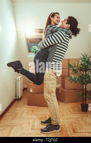 The young couple is moving into a new house. They are hugging happy after bringing boxes with things to their new home. - Stock Photo