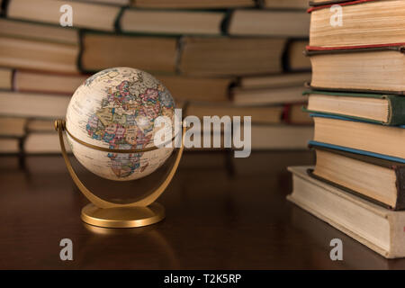 globe and many books on a wooden table - Stock Photo