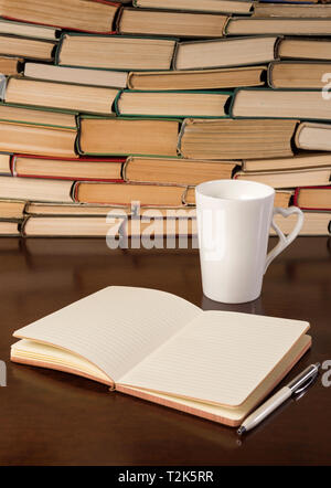 Old books on wooden table with tea and open notebook - Stock Photo
