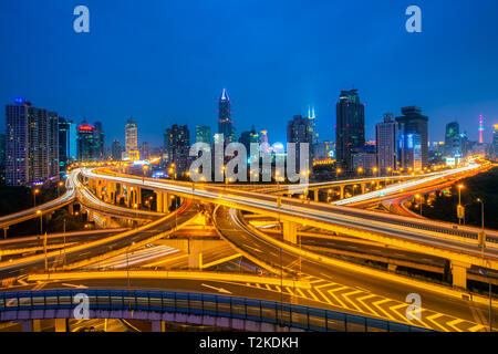 Shanghai elevated road junction and interchange overpass at night in China. - Stock Photo